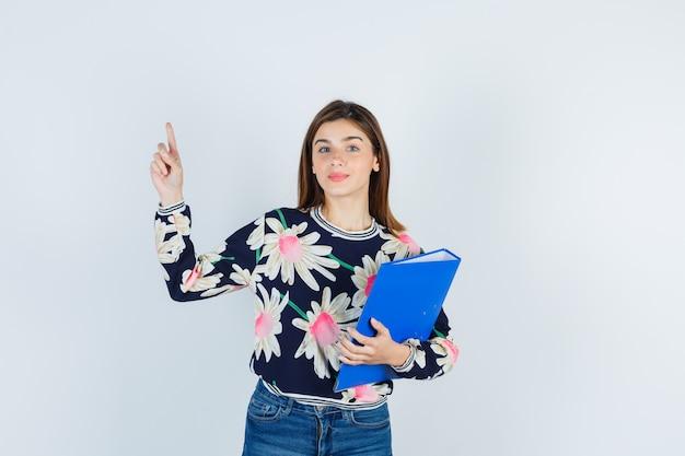 Jeune fille tenant un dossier, pointant vers le haut en blouse florale, jeans et semblant curieuse, vue de face.
