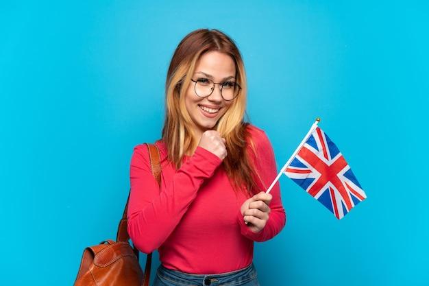 Jeune fille tenant un drapeau du royaume-uni sur fond bleu isolé célébrant une victoire