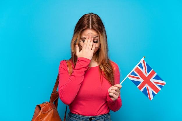 Jeune fille tenant un drapeau du royaume-uni sur fond bleu isolé avec une expression fatiguée et malade