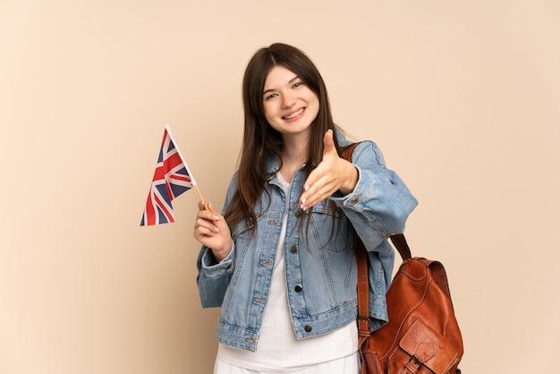 Jeune fille tenant un drapeau du royaume-uni isolé sur beige se serrant la main pour conclure une bonne affaire