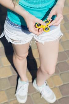 Jeune fille tenant une fidget spinner dans les mains tout en se promenant à l'extérieur