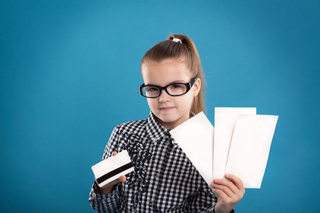 Jeune fille tenant des formulaires vierges et une carte de crédit et souriant