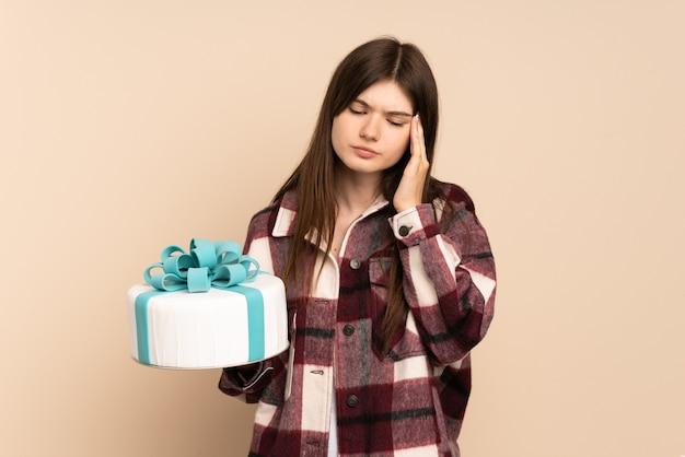 Jeune fille tenant un gros gâteau isolé sur beige avec maux de tête
