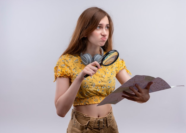Jeune fille tenant une loupe et une carte sur un mur blanc isolé avec espace de copie
