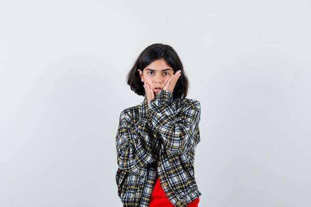 Jeune fille tenant la main sur les joues en chemise à carreaux et t-shirt rouge et l'air surpris, vue de face.