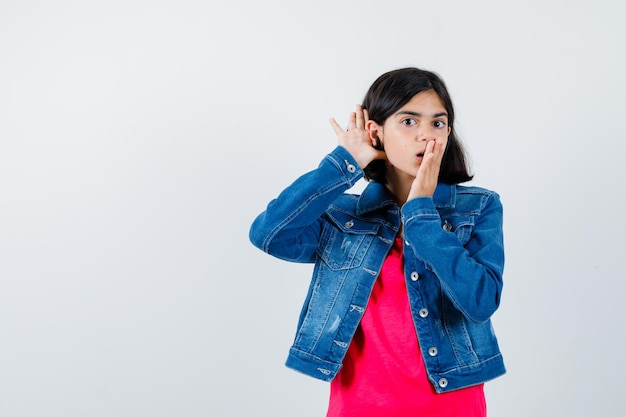 Jeune fille tenant la main près de l'oreille pour entendre quelque chose et couvrant la bouche avec la main en t-shirt rouge et veste en jean et l'air surpris. vue de face.