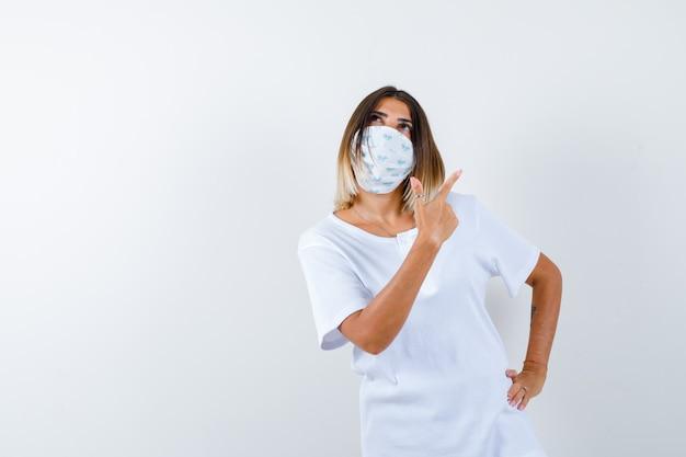 Jeune fille tenant la main sur la taille, pointant vers la droite avec l'index en t-shirt blanc et masque et regardant pensif. vue de face.