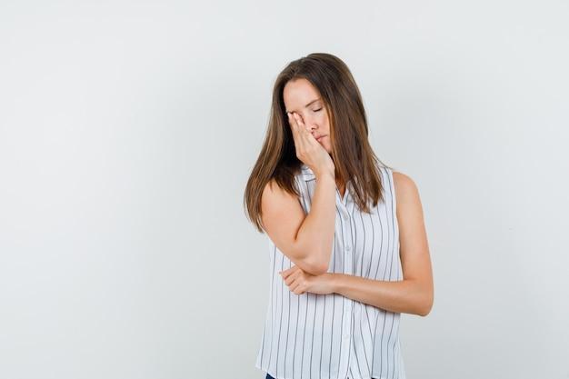 Jeune fille tenant la main sur les yeux en t-shirt, jeans et regardant somnolent, vue de face.