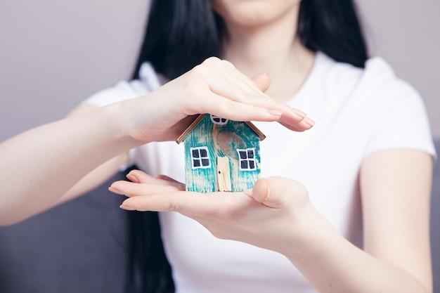 Jeune fille tenant une maison