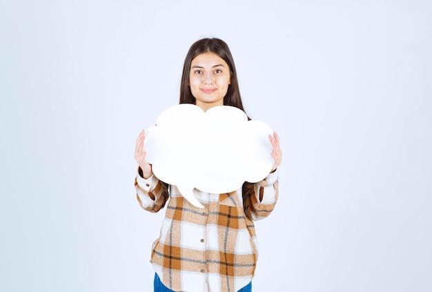 Jeune fille tenant un nuage de texte vide sur un mur blanc.