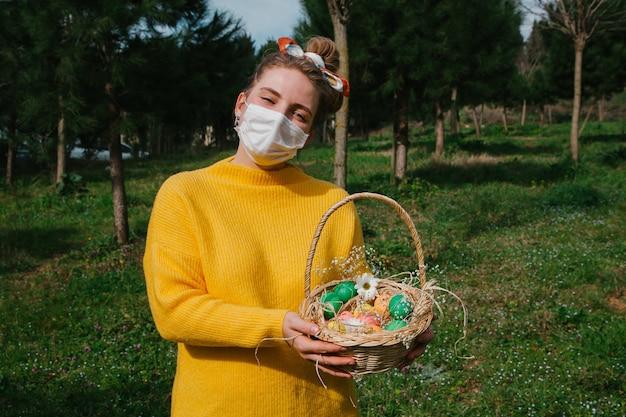 Jeune fille tenant des oeufs de pâques dans le panier avec des fleurs et des bonbons