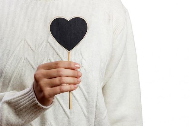 Jeune fille tenant un panneau de coeur noir