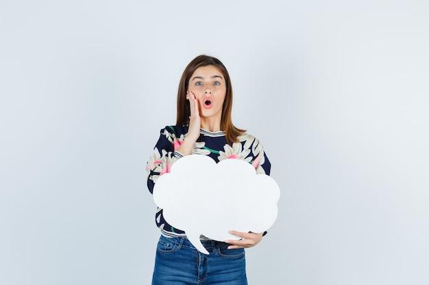 Jeune fille tenant la paume sur la joue en blouse florale, jeans et l'air choqué, vue de face.