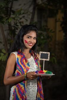 Jeune fille tenant une petite planche et une couleur poudrée à l'occasion du festival holi.