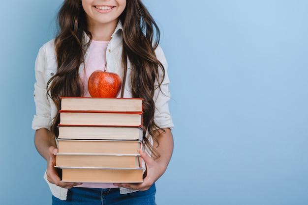 Jeune fille tenant une pile de livres avec apple à ce sujet. retour à l'école.