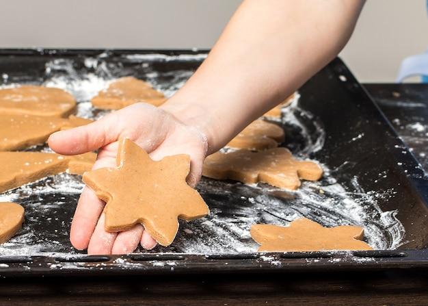 Jeune fille tenant une plaque de cuisson avec des biscuits au gingembre fraîchement cuits