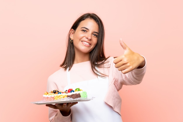 Jeune fille tenant plein de mini-gâteaux différents sur un mur isolé avec les pouces vers le haut parce qu'il s'est passé quelque chose de bien