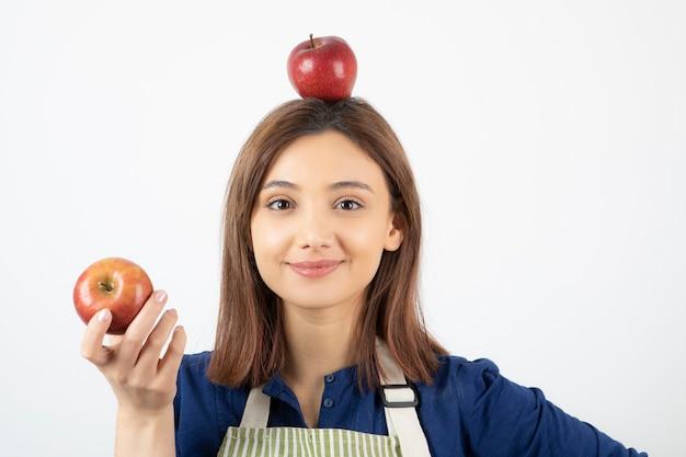 Jeune fille tenant des pommes rouges tout en souriant sur blanc.