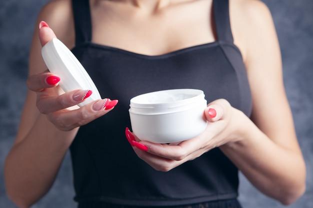 Une jeune fille tenant un pot de crème dans ses mains
