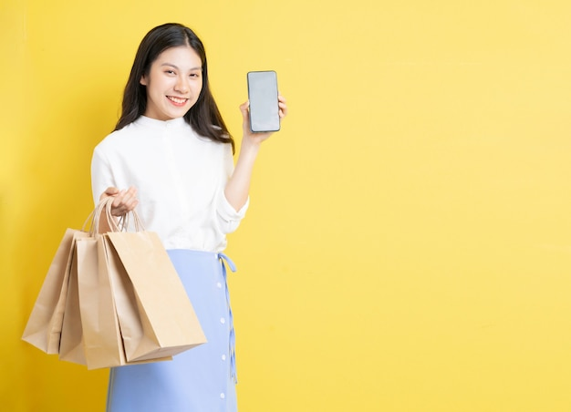 Jeune fille tenant un sac à provisions avec une expression heureuse utilise un téléphone sur fond jaune