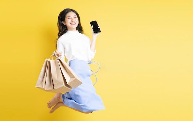 Jeune fille tenant un sac à provisions avec une expression joyeuse sautant sur fond jaune