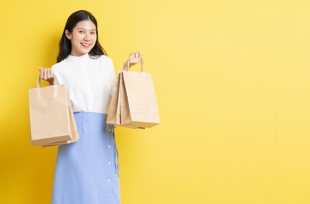 Jeune fille tenant un sac à provisions avec un visage heureux sur fond jaune