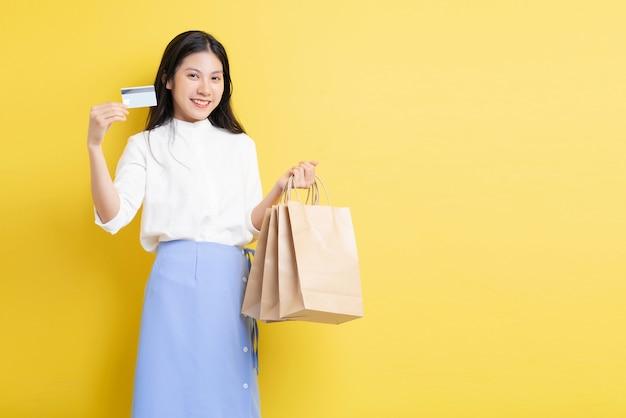 Jeune fille tenant un sac à provisions avec un visage heureux main tenant une carte de crédit sur fond jaune