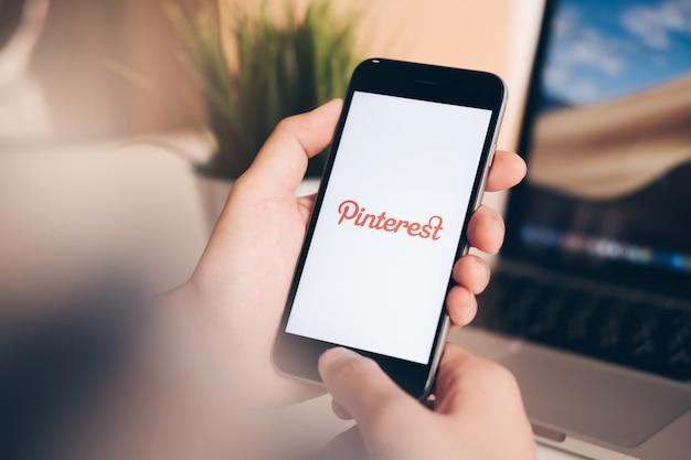 Jeune fille tenant un smartphone avec les médias sociaux à l'écran