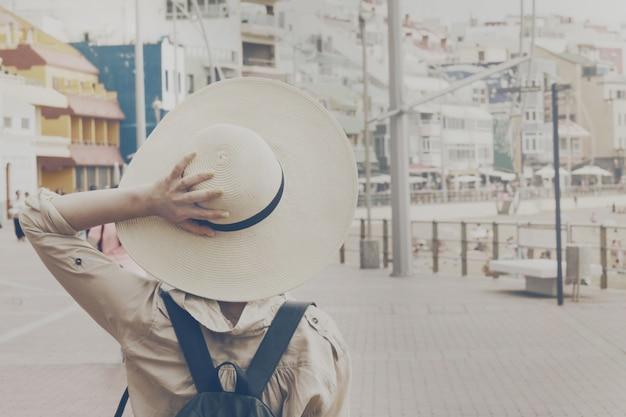Jeune fille tenant son chapeau de paille en train de marcher dans la rue. urban travel vacation summer concept. toning. mise au point sélective.