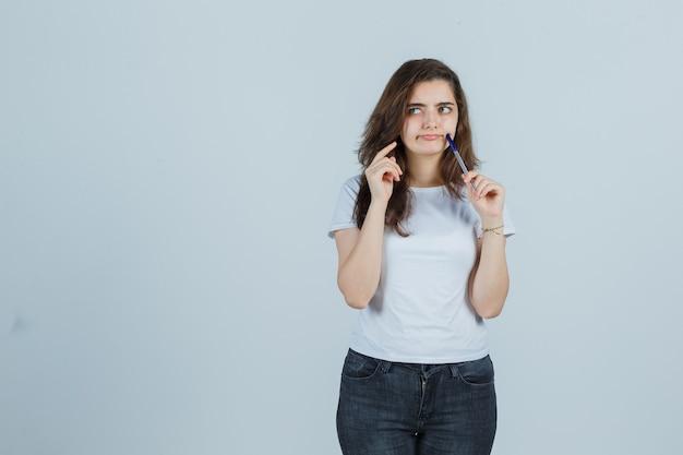 Jeune fille tenant un stylo sur la joue en t-shirt, jeans et à la vue réfléchie, de face.