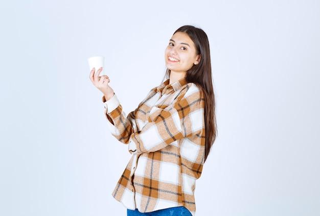 Jeune fille tenant une tasse de thé sur un mur blanc.