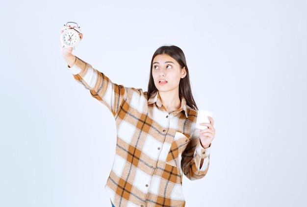 Jeune fille tenant une tasse de thé et regardant l'heure sur un mur blanc.