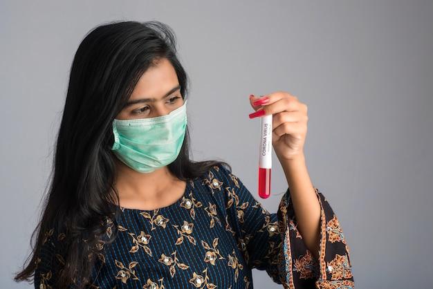 Jeune fille tenant un tube à essai avec un échantillon de sang pour le coronavirus ou l'analyse 2019-ncov.