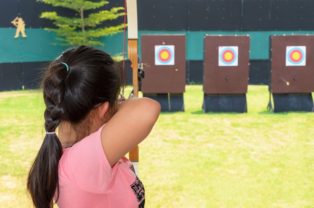 Jeune fille tenant et visant l'arc dans le champ de pratique
