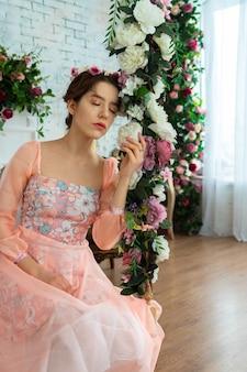 Une jeune fille tendre à l'image d'une princesse dans une robe rose avec une couronne sur la tête est assise sur une balançoire avec des fleurs.