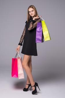 Jeune fille tendre en robe noire et talons hauts détiennent des sacs à provisions