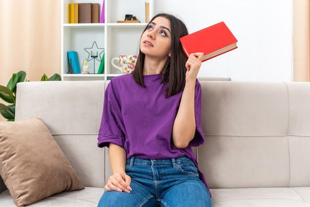 Jeune fille en tenue décontractée tenant un livre jusqu'à perplexe assis sur un canapé dans un salon lumineux