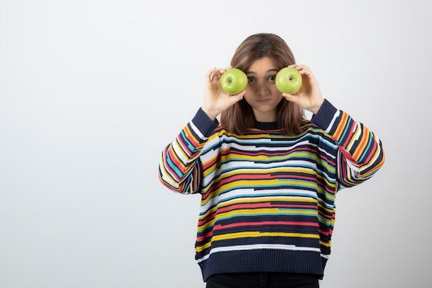 Jeune fille en tenue décontractée tenant des pommes vertes devant les yeux.