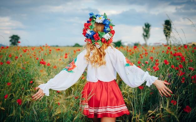 Une jeune fille en tenue nationale lumineuse et avec une couronne de fleurs sur la tête, écartant les bras, traverse un champ de coquelicots rouges