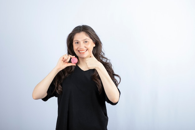 Jeune fille en tenue noire tenant un cookie rose et montrant le pouce vers le haut.