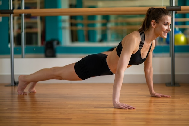 Jeune fille en tenue de sport dans un club de remise en forme se dresse en planche