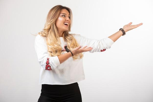 Jeune fille en tenue de sport pointant quelque chose sur la droite