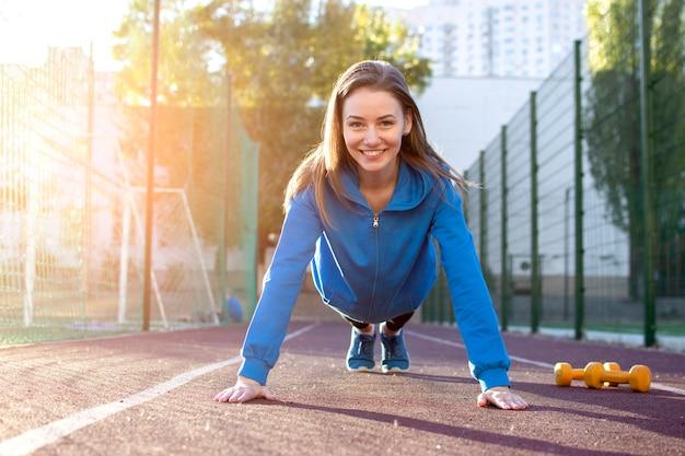 Jeune fille en tenue de sport se soulève du sol sur un tapis roulant