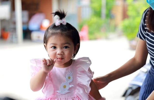 Jeune fille thaïlandaise avec du sucre et une douce expression. une jeune fille mange des bonbons.