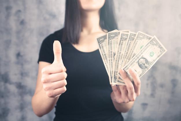 La jeune fille tient de l'argent dans ses mains et montre son pouce vers le haut