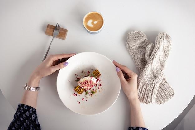 La jeune fille tient une assiette avec un gâteau, à côté des mitaines. la vue du haut. concept d'hiver, de chaleur, de vacances, d'événements. flou artistique.