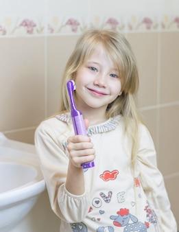 La jeune fille tient une brosse à dents électrique à la main.