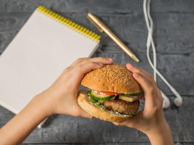 La jeune fille tient un burger fraîchement préparé sur une table avec un stylo, un ordinateur portable et des écouteurs
