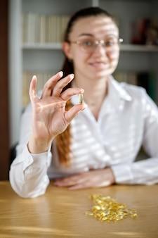 La jeune fille tient une capsule d'huile de poisson dans sa main. capsules d'oméga-3 sur la table et dans la main du médecin.