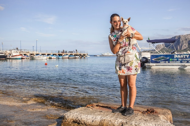 Une jeune fille tient un chihuahua dans ses bras alors qu'elle marche joyeusement